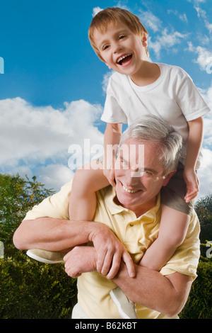Hauts homme portant son petit-fils sur ses épaules et souriant Banque D'Images