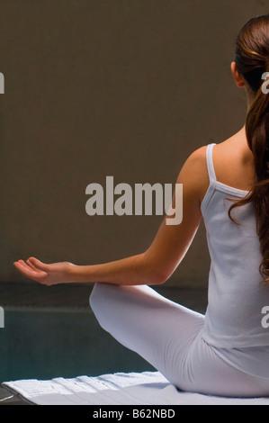 Vue arrière d'une jeune femme méditant au bord de l'eau Banque D'Images
