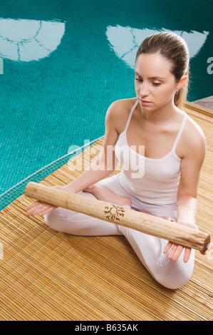Jeune femme méditant au bord de l'eau Banque D'Images
