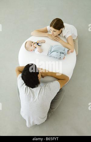 Les jeunes parents appuyé contre un pouf, regardant bébé couché entre eux