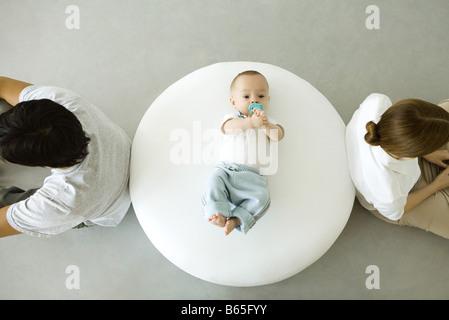 Bébé couché sur un pouf, mère et père assis avec dos tourné, overhead view