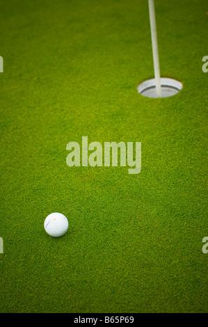Balle de golf près de la tasse sur le vert. Banque D'Images