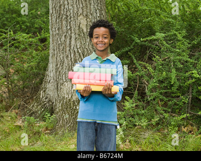 Portrait of a Boy holding a stack of books Banque D'Images