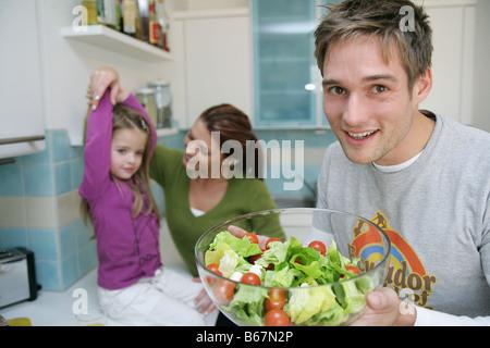 Jeune famille préparer une salade dans une cuisine domestique, Munich, Allemagne Banque D'Images