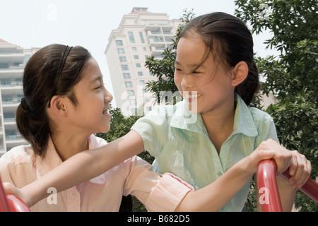 Jeune fille et sa sœur jouant sur un manège Banque D'Images