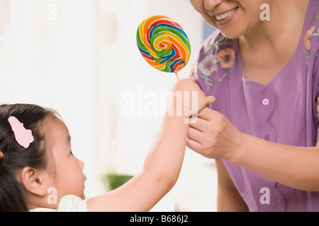 Close-up of a young woman giving a candy à sa petite-fille Banque D'Images