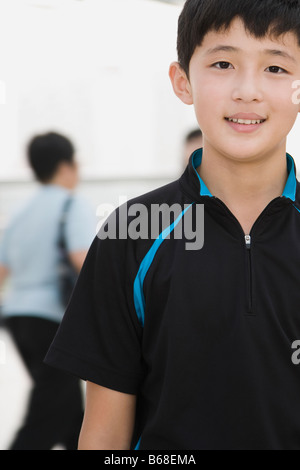 Portrait of a Teenage boy standing in a corridor and smiling Banque D'Images