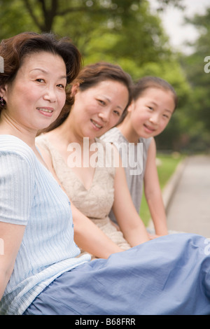 Portrait of a family sitting and smiling in a garden Banque D'Images