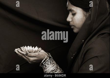 Femme indienne offrant un Nymphaea nénuphar Tropical flower. Sépia Banque D'Images