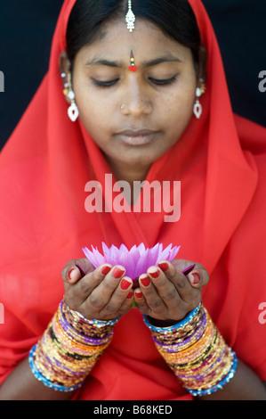Femme indienne offrant un Nymphaea nénuphar Tropical flower dans un sari rouge Banque D'Images