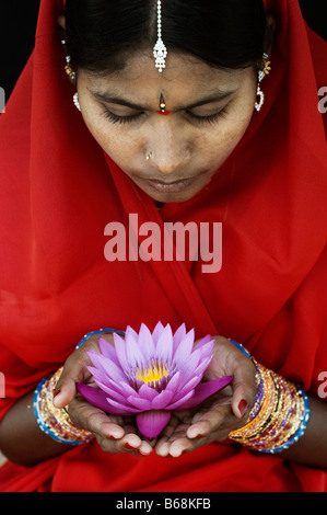 Femme indienne offrant un Nymphaea nénuphar Tropical flower dans un sari rouge. L'Andhra Pradesh, Inde Banque D'Images