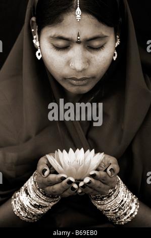 Femme indienne offrant un Nymphaea nénuphar Tropical flower. Sépia. L'Andhra Pradesh, Inde Banque D'Images