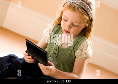 Petite fille jouant un jeu d'ordinateur de poche Banque D'Images