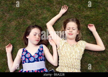 Girls lying on grass with earphones Banque D'Images