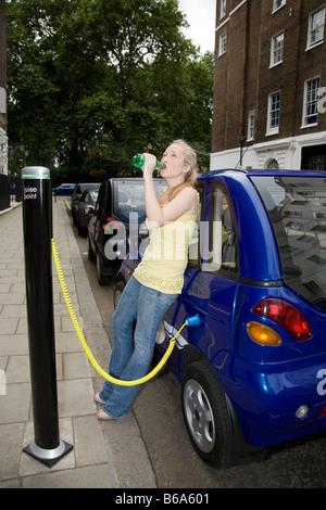 Jeune femme à boire en voiture électrique