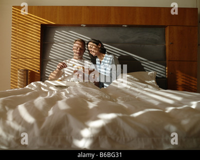 Couple having breakfast on bed Banque D'Images