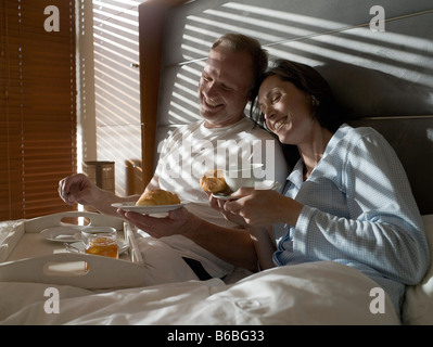 Couple having breakfast sur bed and smiling Banque D'Images