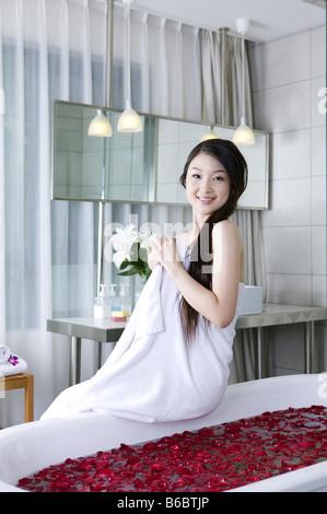 Jeune femme portant une serviette et assis sur la baignoire Banque D'Images