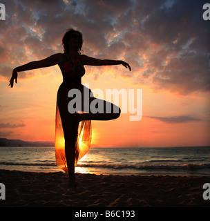 Woman doing yoga exercice sur la plage au coucher du soleil d'ossature Banque D'Images