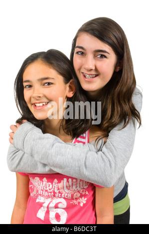 Close up portrait of Vertical de deux sœurs adolescentes, la sœur aînée de donner la plus jeune une accolade, sur Banque D'Images