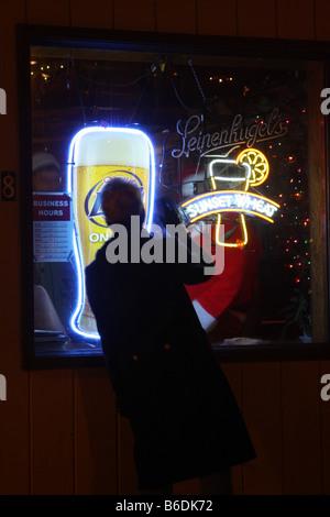 Une femme en agitant au Père Noël assis dans la fenêtre d'un bar dans le Wisconsin avec Leinenkugels et Miller Lite Beer signs