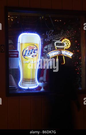 Un homme déguisé en Père Noël assis dans la fenêtre d'un bar avec Leinenkugels et Miller Lite Beer signe au Wisconsin