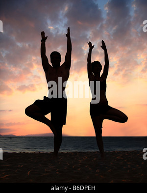 Couple doing yoga exercice sur la plage Banque D'Images