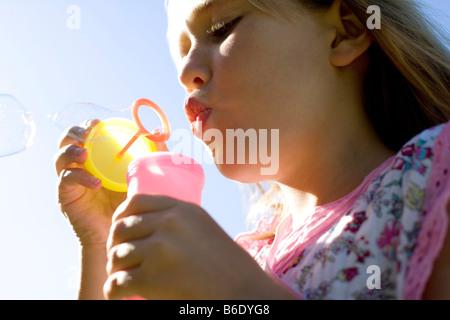 Girl blowing des bulles de savon grâce à une baguette. Banque D'Images