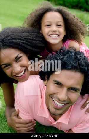 Famille heureuse. Les parents avec leur fille sur l'herbe. Banque D'Images