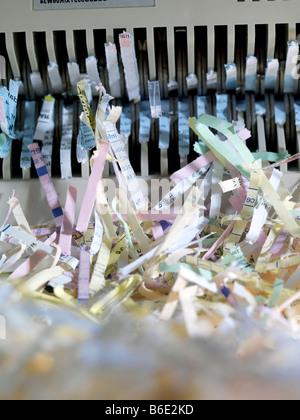 Papier déchiqueté qui sortent d'une déchiqueteuse. Banque D'Images