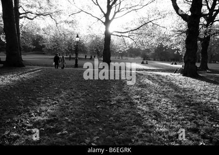 Un couple en train de marcher à travers de longues ombres sur un après-midi d'automne dans la région de Green Park, Banque D'Images