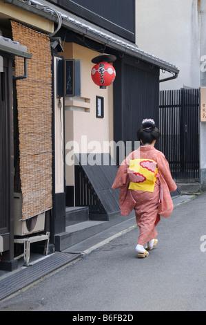 Une Maiko, une Geisha stagiaire, marchant dans le quartier de Gion en allant à l'Odori, Kyoto, Japon, Asie Banque D'Images