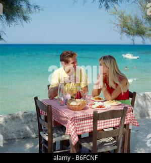 En Grèce, jeune couple boire et manger en plein air au bord de la mer Taverna