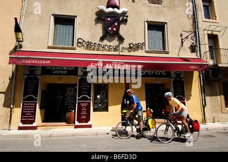 Les cyclistes passant d'une cave à vin à Chauteauneuf du Pape, Provence, France, Europe Banque D'Images