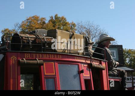Deux cowboys conduisant le Butterfield Overland Stage Coach à travers une vieille ville de l'ouest