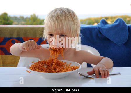 Un jeune garçon de manger des pâtes au cours de vacances en Italie. Banque D'Images