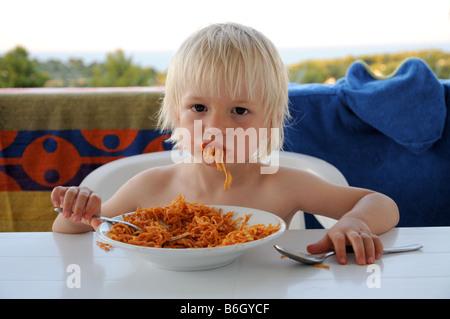 Un jeune garçon de manger des pâtes en vacances en Italie. Banque D'Images