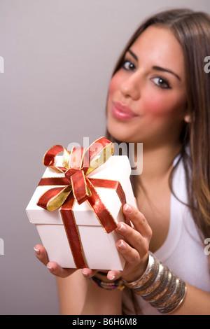 Jolie jeune femme offrant un présent Banque D'Images
