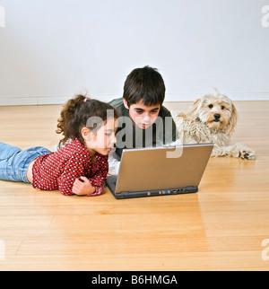 Deux enfants et un chien avec un ordinateur portable sur le sol Banque D'Images