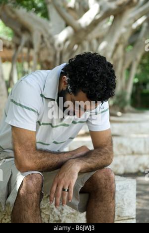 Triste homme assis dans le parc Banque D'Images