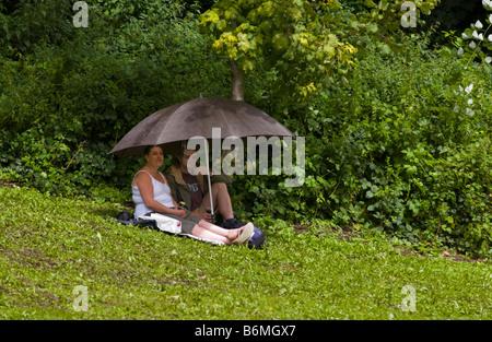 Couple à l'abri de la pluie sous égide dans la boue Bishops Garden Festival de Jazz 2008 à Brecon Powys Pays de Galles UK