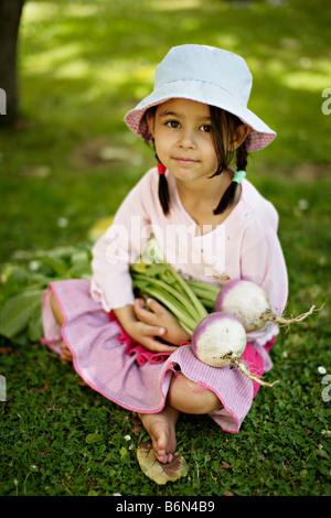 Petite fille de cinq ans tient deux navets cultivés bio