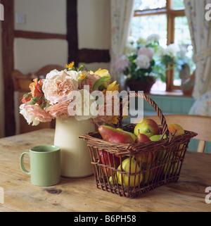 Close-up of roses pastel blanc en pot sur table avec bol vert et panier de pommes Banque D'Images