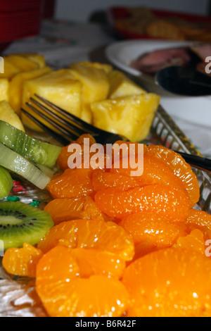 Fruits coupés disposés sur plateau avec les mandarines, les kiwis, fourche plan intermédiaire, et l'ananas. Banque D'Images