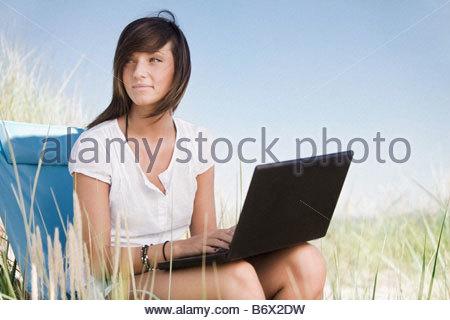 Fille avec l'ordinateur on beach Banque D'Images