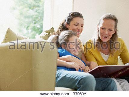 Famille à la recherche d'un album de photos Banque D'Images
