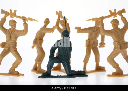 Toy Soldier radio communication inconsciente d'être entouré de soldats ennemis Banque D'Images