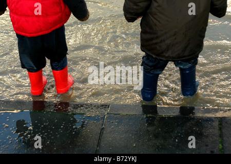 Les enfants portant des bottes Wellington et de jouer dans les flaques d'eau Banque D'Images