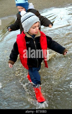 Deux garçons jouant dans les flaques d'eau un jour de pluie avec bottes wellington sur Banque D'Images