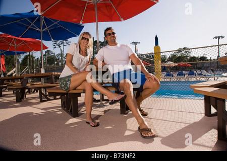 Mid-adult couple assis à une table de pique-nique à la piscine Banque D'Images